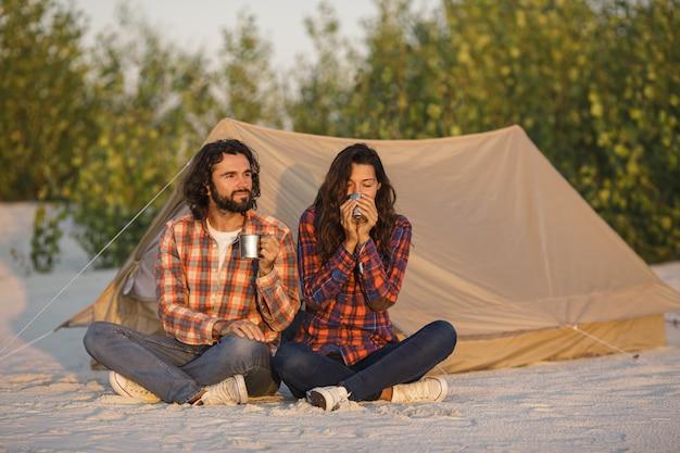 自然に屋外のテントの近くでキャンプ観光カップル