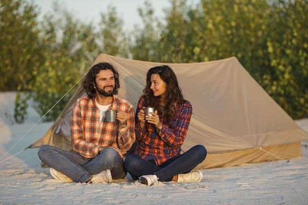 自然に屋外のテントの近くにキャンプ観光カップル