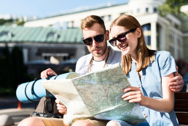 Tourist couple consulting map outdoors