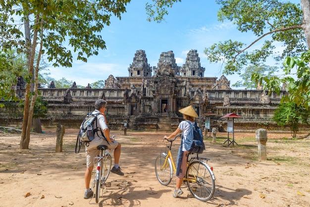 Tourist couple cycling around angkor temple, cambodia. ta keo ruins