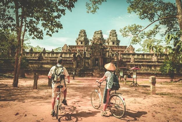 Tourist couple cycling around angkor temple
