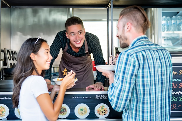 Tourist couple enjoy eating pasta from food truck
