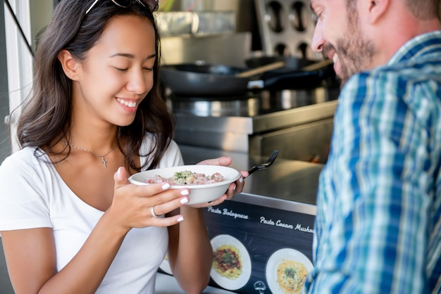 Tourist couple enjoy food at counter of food truck