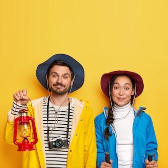 관광 커플은 함께 탐험을하고, 산에서 하이킹을하고, 트레킹 스틱을 사용하고, 사진을 만들기 위해 레트로 카메라를 사용하고, 활동적인 옷을 입고, 모자를 쓰고, 노란색 벽 위에 절연되어 있습니다.