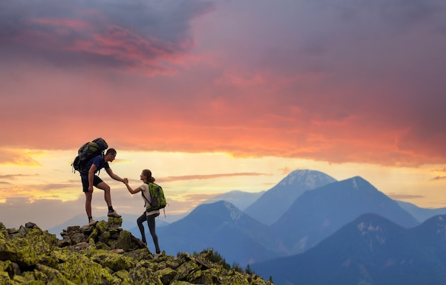 Tourist couple helping each other to climb high rock in evening mountains at sunset.