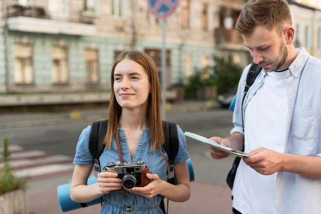 Tourist couple holding camera and map