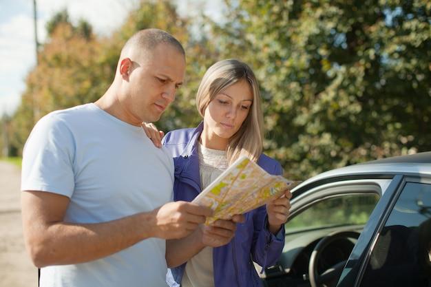 Туристическая пара, глядя на карту
