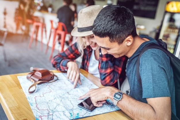 Туристическая пара, наблюдая карту за столом