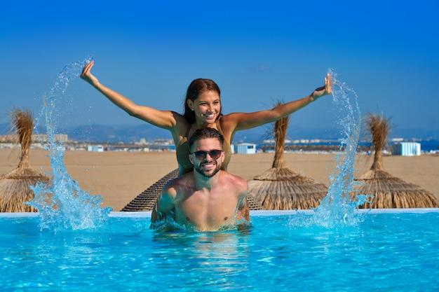 Tourist couple piggyback in infinity pool