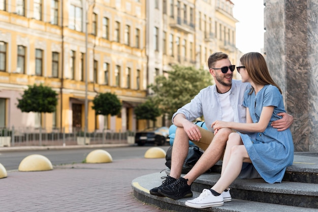 Tourist couple posing embraces on steps outdoors