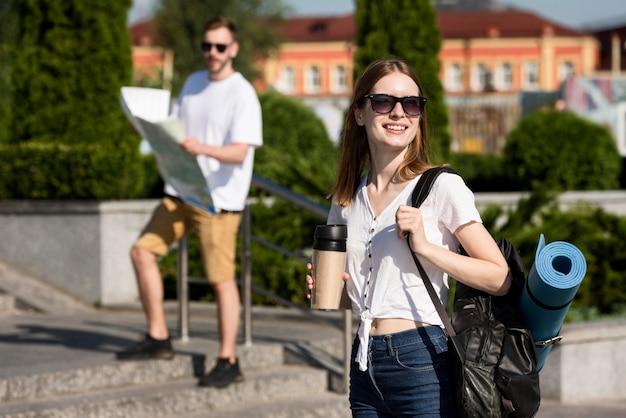 Туристическая пара позирует на открытом воздухе с рюкзаками