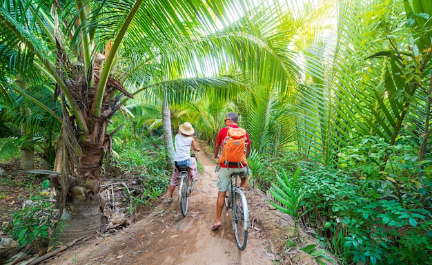 Tourist couple riding bicycle in the mekong delta region, ben tre, south vietnam. woman and man having fun cycling on trail among green tropical woodland and coconut palm trees. rear view.