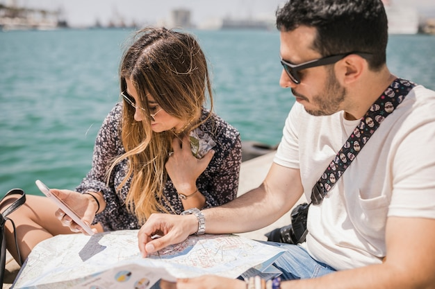 Tourist couple searching direction on cell phone and map