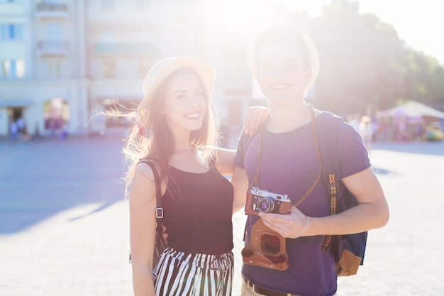 Tourist couple sightseeing in city with sun effect
