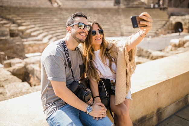 Tourist couple sitting together taking selfie through cell phone