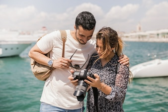 Tourist couple standing near the sea looking at camera