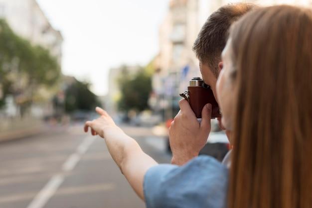 街の写真を撮る観光客カップル