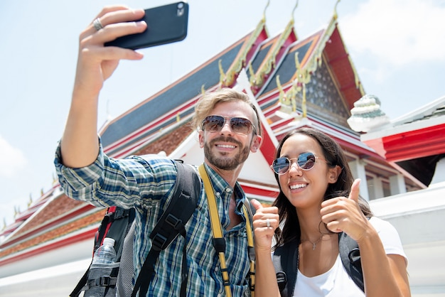 Tourist couple taking selfie at thai temple on vacations in thailand