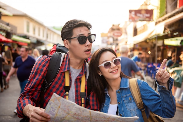 Tourist couple using map while traveling in khao san road bangkok thailand