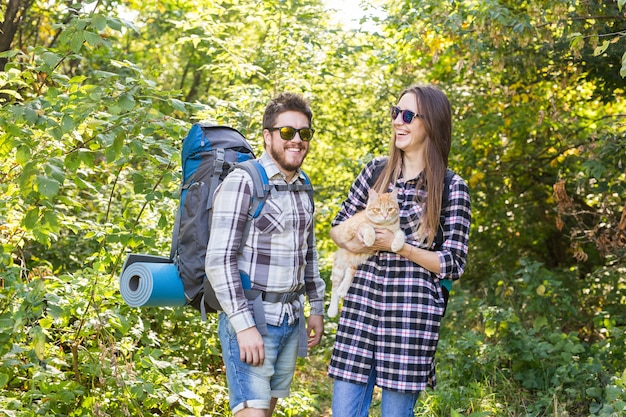 Tourist couple with cat walking in the woods