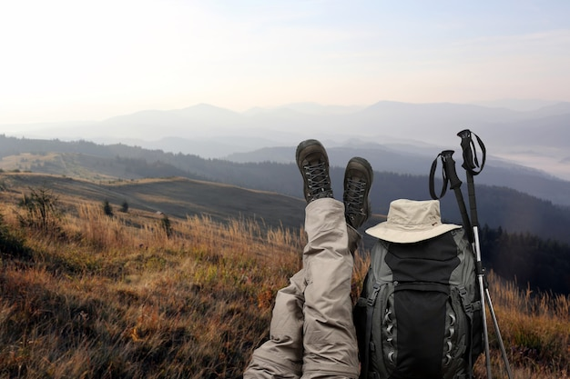 The tourist crossed her legs up near a backpack in nature