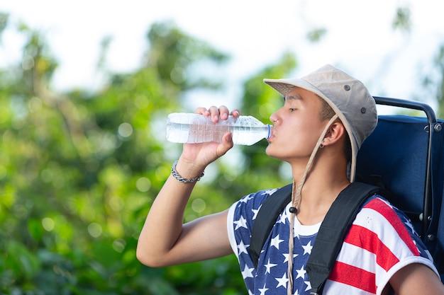 田舎のボトルから水を飲む観光客