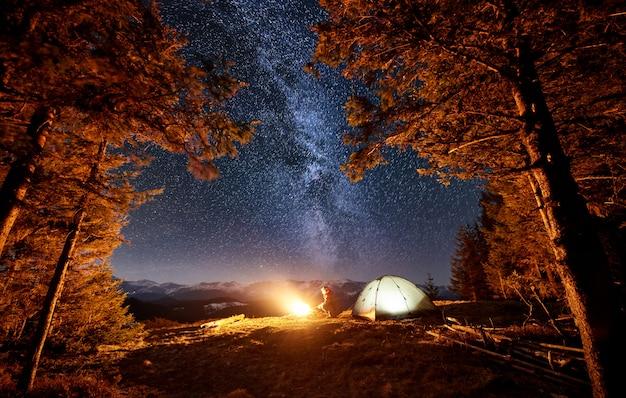 Турист наслаждается в своем лагере возле леса ночью