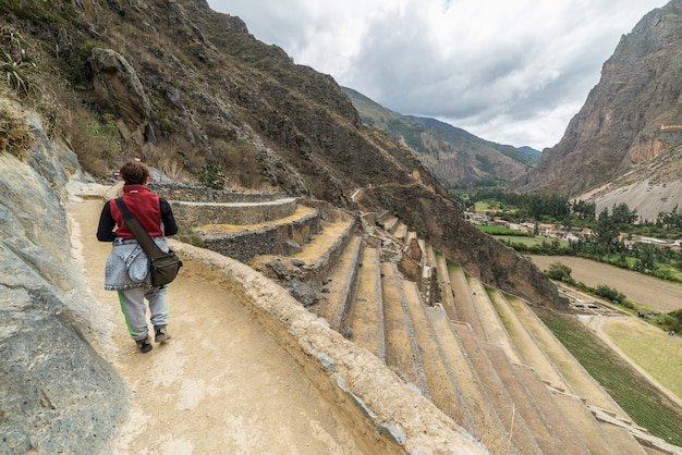 Tourist exploring the inca trails and the archaeological site at ollantaytambo, sacred valley, travel destination in cusco region, peru. vacations and adventures in south america.