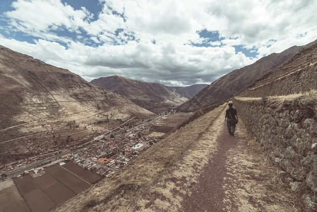 Tourist exploring the inca trails and the majestic terraces of pisac, sacred valley, major travel destination in cusco region, peru. vacations and adventures in south america.