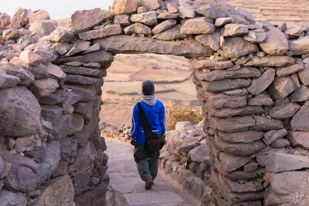 Tourist exploring inca trails at sunset on amantani' island, titicaca lake, among the most scenic travel destination in peru. travel adventures and vacations in the americas.