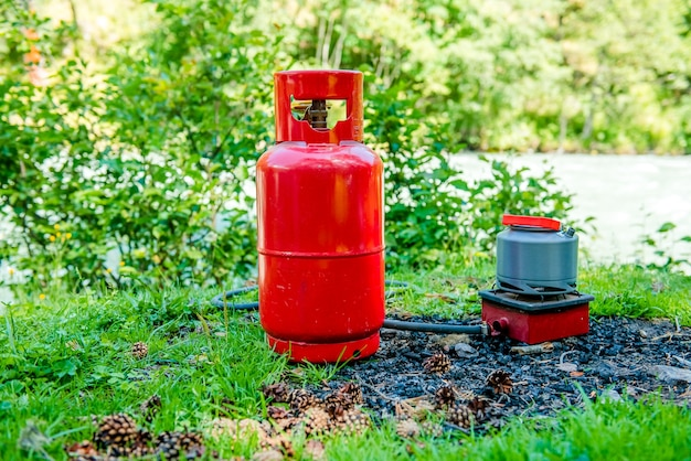 Tourist gas kettle in nature a kettle boiling on a camping stove to make tea while camping