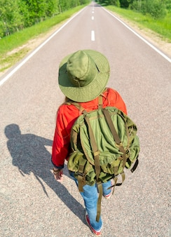 Tourist girl on the asphalt road.