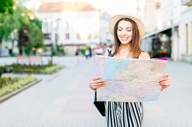Tourist girl in city with map