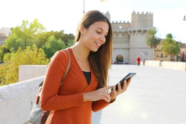バックパックと携帯電話でバレンシアの街を探索する観光女の子