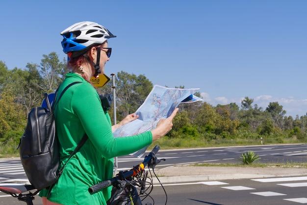 自転車の道路の交差点で地図を調べる自転車のヘルメットをかぶった観光客の女の子