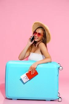 Туристическая девушка в летней одежде с багажом держит деньги на билет на паспорт во время разговора по телефону