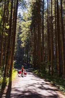 舗装された自転車道の周りの森を眺める自転車に乗った観光客の女の子。舗装された道路に立っているサドルバッグを持つサイクリスト