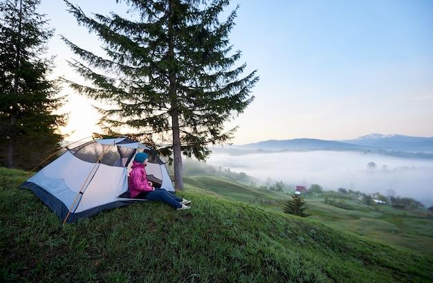 観光テントの入り口に一人で座っている観光客の女の子