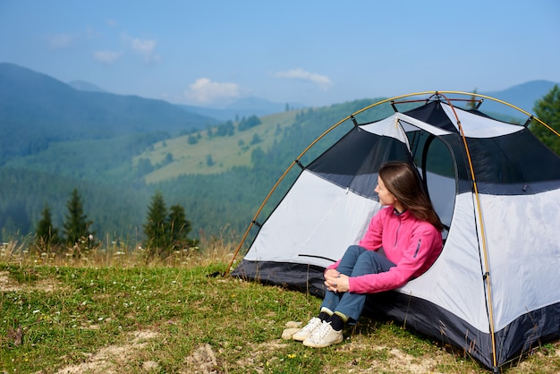 Tourist girl sitting in the entrance of small tent and enjoying beautiful foggy mountains covered with forest view under clear blue sky on bright summer morning