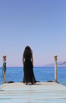 관광 소녀는 바다가 보이는 목조 부두에 다시 서 있다