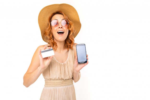 Tourist girl in a summer dress and hat holds a credit card with a mockup and a smartphone for ordering a tour on a white background