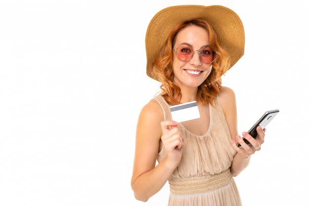 Tourist girl in a summer dress and hat holds a credit card with a mockup and a smartphone for ordering a tour on a white