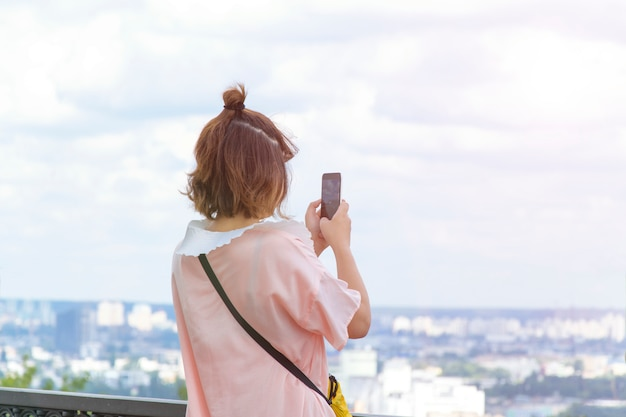 Tourist girl takes pictures on the phone view of the city
