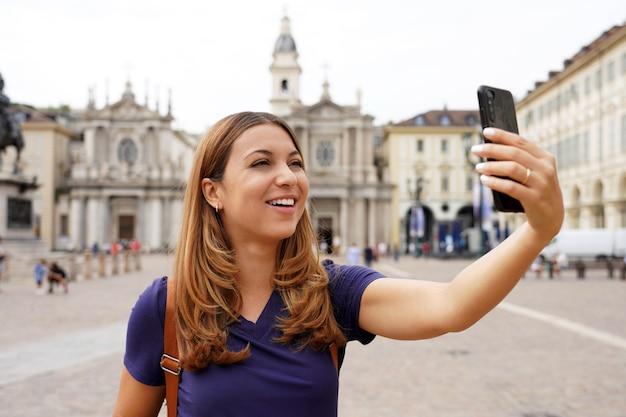 Туристическая девушка видеозвонок и демонстрация городского пейзажа во время ее путешествия по европе. молодая женщина-путешественница на городской площади делает селфи или делится своим опытом в видеоблоге, турин, италия.