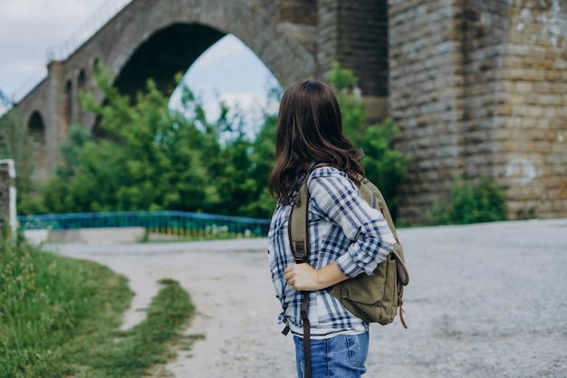 Tourist girl with a backpack on stone bridge.