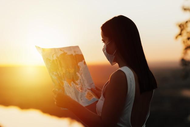 Туристическая девушка с маской для лица, глядя маршрут на карте. она носит маску для лица, новую нормальную концепцию путешествий.