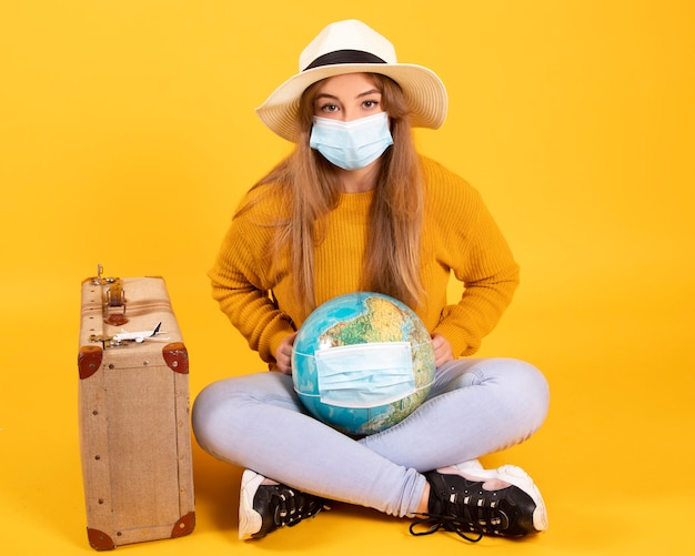 A tourist girl with a medical mask, has a suitcase, a globe, is willing to travel but the covid-19 prevents it