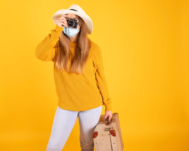 A tourist girl with a medical mask, suitcase, camera hat cannot travel by covid-19