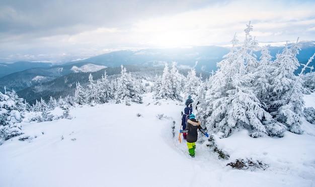 ルートに沿ってトレッキングする雪山の観光客グループ