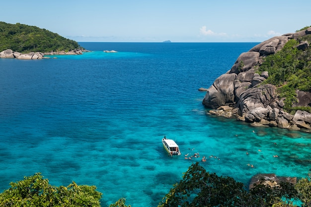 Tourist group snorkeling at coral reef with clear blue ocean water in tropical clear sea in summer, similan island, phang nga,